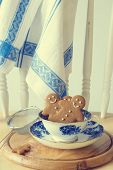 Homemade gingerbread men sitting in a vintage teacup