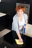 Woman cleaning the kitchen. Adult woman washing glass table