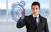 Composite image of businessman standing and pointing to a clock