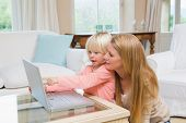 Cute daughter and mother using laptop on coffee table at home in the living room