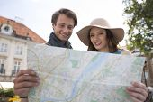Happy tourist couple reading map outdoors