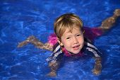Swimming lessons: Cute baby girl is learning how to swim in the pool