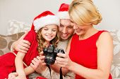 family, christmas, x-mas, happiness and people concept - smiling family in santa helper hats looking