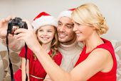 family, christmas, x-mas, happiness and people concept - smiling family in santa helper hats taking