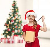 christmas, x-mas, winter, happiness concept - smiling girl in santa helper hat with gift box and mag