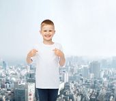 advertising, people and childhood concept - smiling little boy in white blank t-shirt pointing fingers at himself over city background
