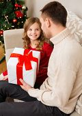 family, christmas, x-mas, happiness and people concept - smiling father and daughter holding gift bo