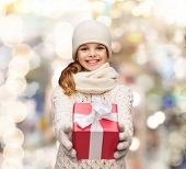 christmas, holidays, childhood, presents and people concept - dreaming girl in winter clothes with g