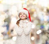 christmas, holidays, childhood and people concept - smiling girl in santa helper hat over lights background