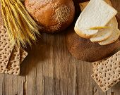 assortment of bread (rye, whole wheat, for toast) on wooden background