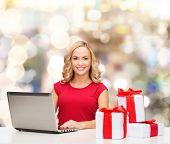 christmas, holidays, technology, advertising and people concept - smiling woman in red blank shirt with gifts and laptop computer over lights background