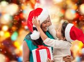 christmas, holidays, celebration, family and people concept - happy mother and child girl in santa h