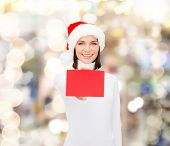 christmas, holdays, people, advertisement and sale concept - happy woman in santa helper hat with bl