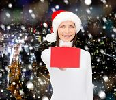 christmas, holidays, people, advertisement and sale concept - happy woman in santa helper hat with b