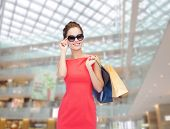 shopping, sale, christmas and holiday concept - smiling elegant woman in red dress and sunglasses wi