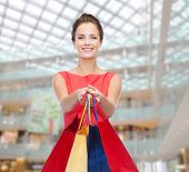 shopping, sale, christmas and holiday concept - smiling elegant woman in red dress with shopping bag