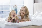 Portrait of happy mother and daughter lying in bed