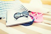 beach, summer, vacation, accessories and technology concept - close up of laptop and summer accessor