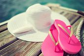 beach, summer, vacations and accessories concept - close up of hat, sunscreen and slippers at seasid