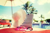 beach, summer vacation and accessories concept - close up of hat, bag, sunscreen and sunglasses at pool