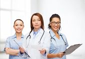 healthcare and medicine concept - calm female doctor and nurses with clipboard and stethoscope givin
