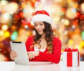 christmas, holidays, technology and people concept - smiling woman in santa helper hat with gift box