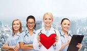 healthcare and medicine concept - smiling female doctor and nurses with red heart