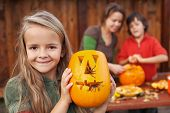 stock photo of halloween  - Little girl showing her freshly carved Halloween jack - JPG