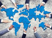 Group of Business People with Jigsaw Puzzle Forming in World Map