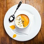 Pumpkin Soup With Cream And Pumpkin Seeds In A White Bowl On Wooden Table