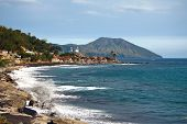 Picturesque Ancient City With Mosque At The Seaside With A Volcano Ab A Background