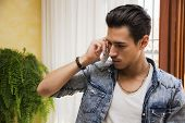 Handsome young man talking on telephone inside house