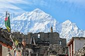 Ruins Of Ancient Buddist Temple High In The Mountains In Himalayas With A Snowy Mountain Peak On The