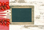Wooden Kitchen Utensils With Red Tomatoes And Blackboard