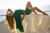 Sexy Woman With Blond Hair In Elegant Green Dress Posing On Yacht