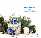 Blue And Silver Christmas Balls In A Cage On The Background Of Fir Branches And Candles