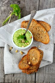 stock photo of pine nut  - Green pea hummus with pine nuts and thin croutons on wooden table with linen napkin