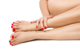 stock photo of pedicure  - Beautiful long female bare sexy legs with red pedicure female foots with red pedicure and hands with red manicure close up isolated - JPG