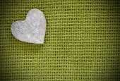 Wooden heart on a green fabric background