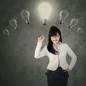 Creative Female Manager Pointing At Lightbulb