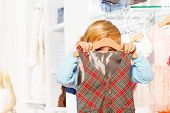 Close-up view of boy hiding behind hanger and vest