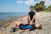 foto of cpr  - Two women carrying out First aid training for Scuba divers on a beach - JPG