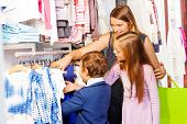 picture of women rights  - Woman with two children shopping together in the clothes store and choosing the right clothing item - JPG