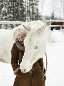 foto of feeding horse  - Attractive blond woman feeds a white horse overcast winter day - JPG