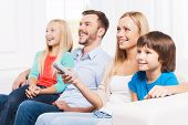 foto of bonding  - Side View of happy family of four bonding to each other and smiling while watching TV at home together - JPG