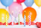 picture of candle flame  - Closeup of colorful birthday candles on a cake with balloons in background - JPG