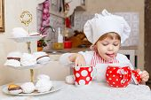 picture of chef cap  - Little girl in apron and cap of the cook with sweet desserts sits at the dining table in the kitchen in the house - JPG