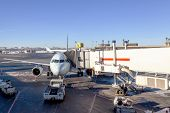 foto of jet  - a passenger plane connected to a jet bridge being serviced by at airport gate - JPG