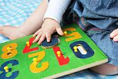 Child Playing With Number Puzzle