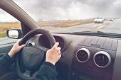 stock photo of steers  - Hands of a female driver on steering wheel of a car on a cloudy winter day - JPG
